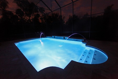A Swimming Pool lit up at night Stock Photo