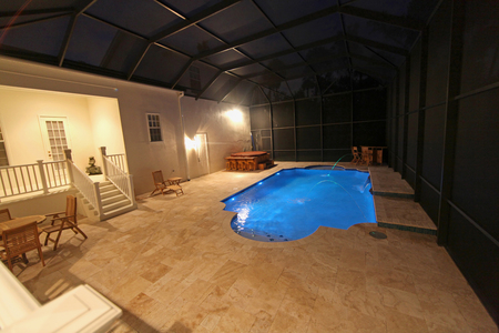 travertine house: A Swimming Pool lit up at night Stock Photo