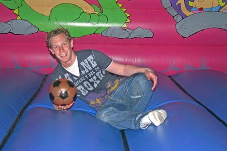 brincolin: Un var�n joven atl�tico con un bal�n de f�tbol Foto de archivo