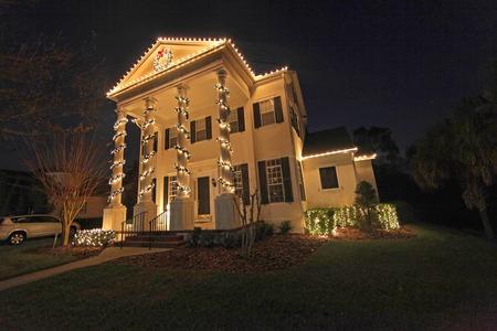 casa colonial: Una casa colonial con un mont�n de luces de Navidad Foto de archivo
