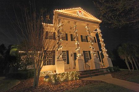 seasonal light display: A Colonial House with a lot of Christmas Lights