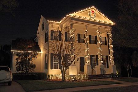 casa colonial: Una casa colonial con un montón de luces de Navidad Foto de archivo