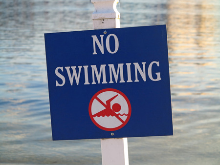 no swimming sign: A sign showing no swimming in the water behind