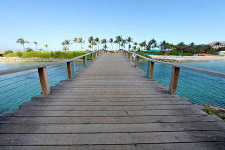 bridge over water: A wooden bridge over water going over to a beach Stock Photo