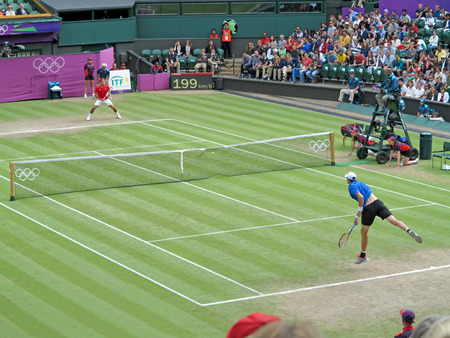 WIMBLEDON, ENGLAND - August 2nd, 2012 – Roger Federer and John Isner during their singles matches at the summer Olympics in London in 2012. Roger Federer came 2nd, silver medal and John Isner made it to the quarterfinals in the tournament Editorial