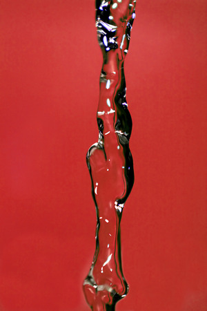 stream  jet: Water falling down, frozen in time with red background. Foto de archivo