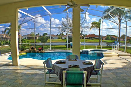 A view from a lanai of a pool, spa and lake.