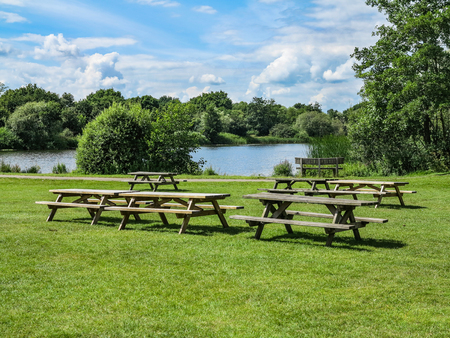 Some picnic tables with a lake and trees behind Stok Fotoğraf