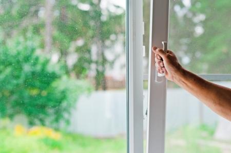 opens: man opens a window Stock Photo