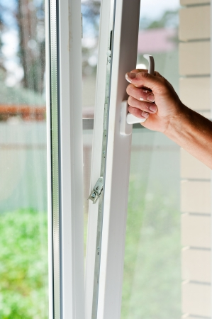 opens: person opens a window with mosquito net Stock Photo