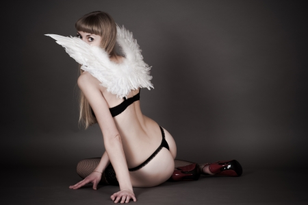 sexy woman with angel wings sitting on the floor photo