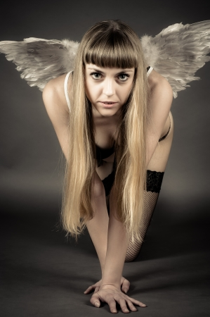 beautiful woman with angel wings kneeling photo