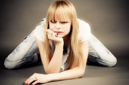 beautiful bangs: cheeky girl sits leaning on elbow Stock Photo