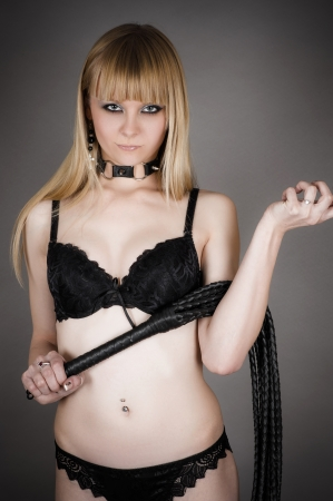 attractive woman in lingerie holding whip