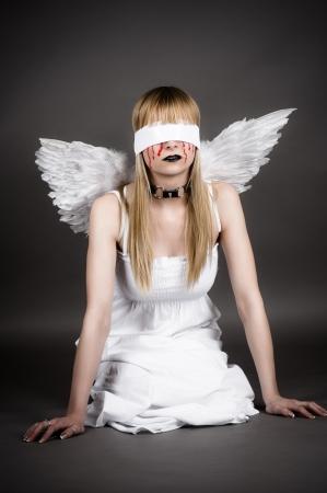fallen angel: fallen angel sitting on the floor