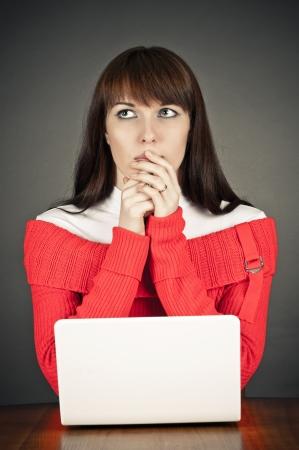 mujer pensativa: Mujer pensativa sentado en la computadora Foto de archivo