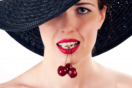 beautiful woman with cherry in mouth photo