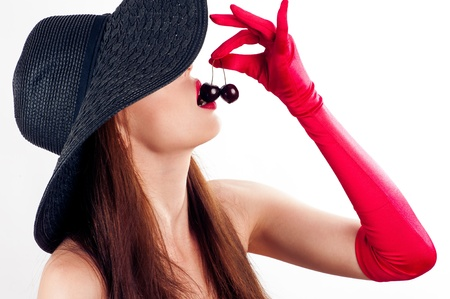 beautiful woman in hat and gloves eating cherries photo