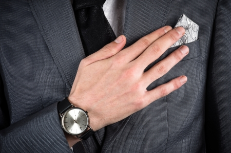 corrects: business man in a suit corrects hand handkerchief Stock Photo