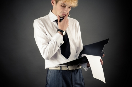 businessman pondering documents: young business man pondered over signing the document