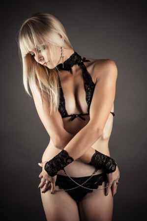 sadistic: sexy woman in lingerie isolated on gray background