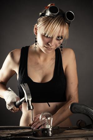 beautiful woman engineer just scored hammering a nail
