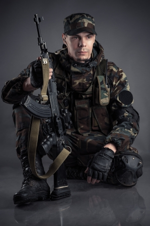 soldier sitting on the floor with arms photo