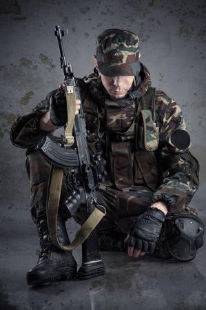 Soldato seduto sul pavimento con le braccia Archivio Fotografico - 24881497