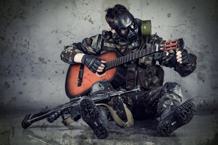 man in gas mask plays guitar