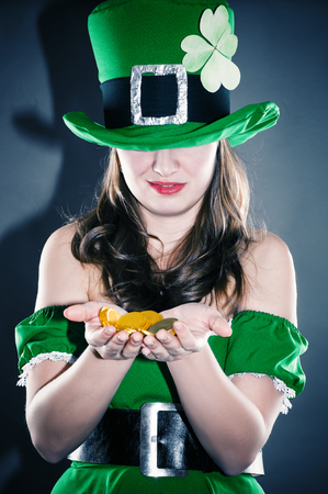 a woman dressed as a leprechaun holding gold coins photo