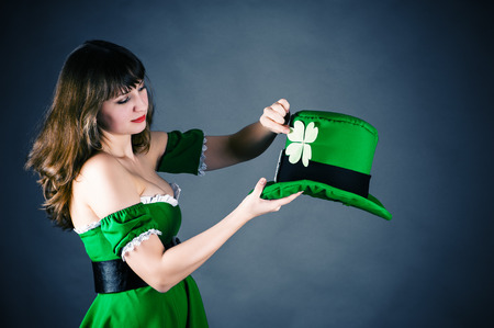 a woman dressed as a leprechaun holding his bowler hat photo