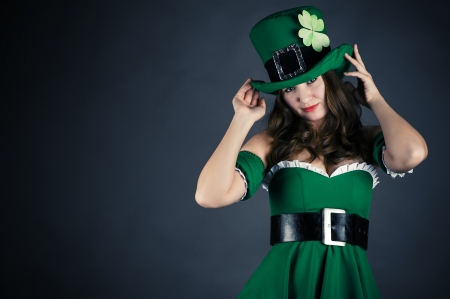 woman dressed as leprechaun isolated on gray background photo