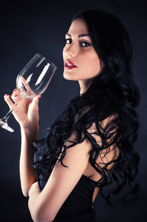 portrait of a beautiful seductive woman with glass in hand photo