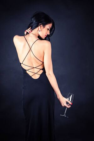 beautiful woman in a black dress with a glass in hand photo