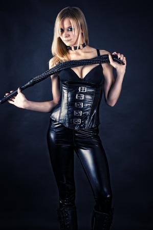 手に持った鞭、コルセットで美しい女性