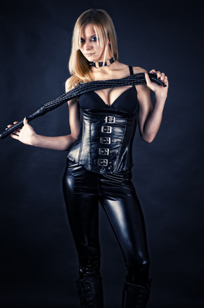 beautiful woman in a corset with a whip in hands Stock Photo