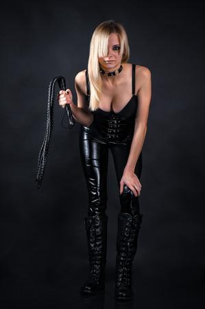 bella mujer en un corsé con un látigo en las manos Foto de archivo