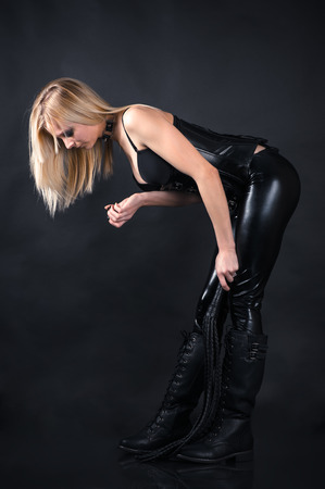 bondage girl: beautiful woman in a corset with a whip in hands Stock Photo
