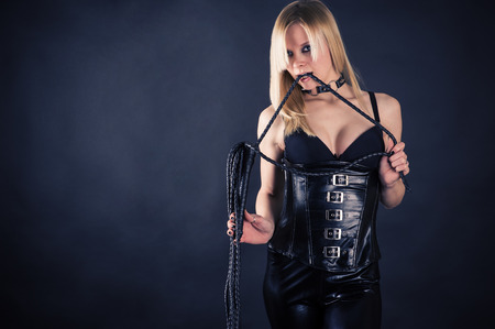 slave girl: beautiful woman in a corset biting whip Stock Photo