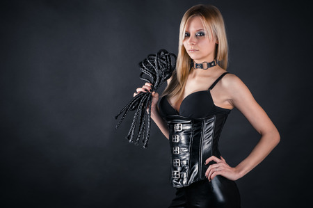 slave girl: beautiful woman in a corset with a whip in hands Stock Photo