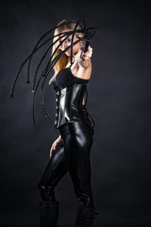 esclavo: bella mujer en un corsé con un látigo en las manos Foto de archivo