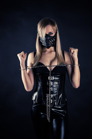 masochism: woman slave in a mask with spikes