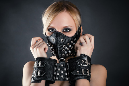 slave woman in handcuffs and a mask with spikes