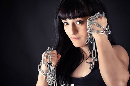 athletic girl in a fighting stance with a chain in hands