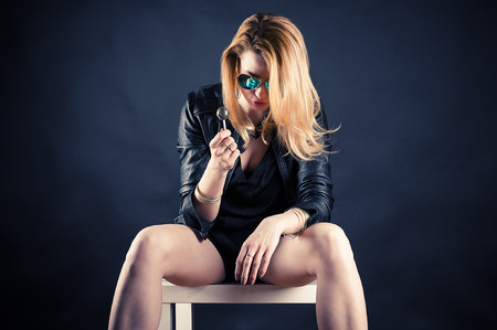 drunk woman with lollipop sitting on a chair photo