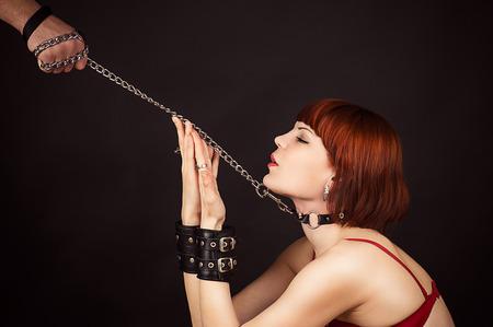 esclavo: bella mujer en el papel de un esclavo con una correa