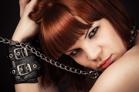 portrait of beautiful brown-haired woman in handcuffs photo