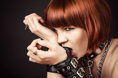 beautiful fashionable woman gnaws leather handcuffs photo