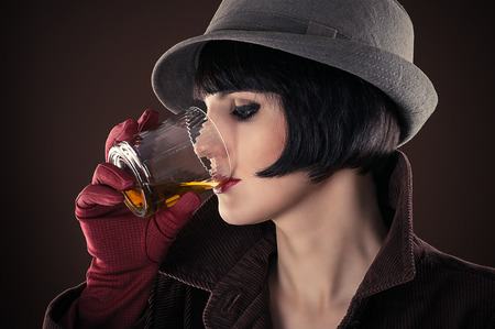 liquor girl: attractive woman detective drinking whiskey from a glass