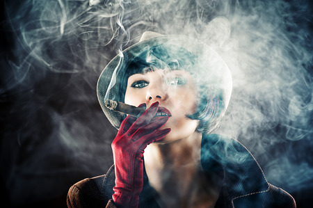 cigar smoking woman: beautiful glamorous woman in retro style with cigar